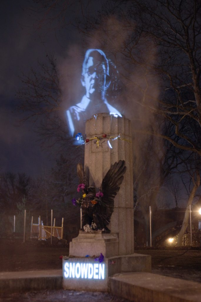 Snowden's face projected and captured in a cloud of smoke